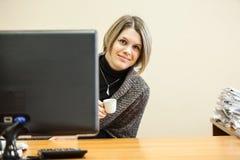 Νέα γυναίκα με το φλυτζάνι καφέ που κοιτάζει από την οθόνη PC, copyspace Στοκ εικόνα με δικαίωμα ελεύθερης χρήσης
