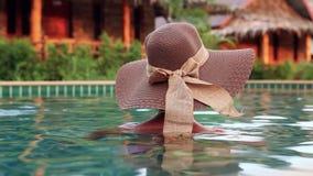 Νέα γυναίκα με το ψαθάκι από πίσω στην πισίνα φιλμ μικρού μήκους