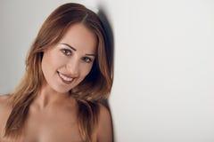 Νέα γυναίκα με το όμορφο χαμόγελο που εξετάζει τη κάμερα στοκ εικόνες