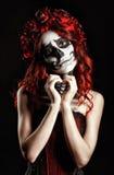 Νέα γυναίκα με το calavera makeup (κρανίο ζάχαρης) που κατασκευάζει την καρδιά να υπογράψει Στοκ εικόνα με δικαίωμα ελεύθερης χρήσης