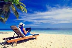 Νέα γυναίκα με το lap-top στην τροπική παραλία Στοκ φωτογραφία με δικαίωμα ελεύθερης χρήσης