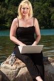 Νέα γυναίκα με το lap-top στη λίμνη Στοκ φωτογραφία με δικαίωμα ελεύθερης χρήσης