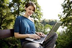 Νέα γυναίκα με το lap-top στο πάρκο Στοκ Εικόνα
