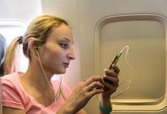 Νέα γυναίκα με το smartphone στο αεροπλάνο στοκ εικόνες
