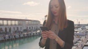 Νέα γυναίκα με το smartphone στο λιμένα γιοτ στο θέρετρο SPA φιλμ μικρού μήκους
