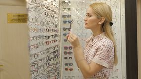 Νέα γυναίκα με Eyeglasses στο οπτικό κατάστημα Όμορφο κορίτσι που φορά τα γυαλιά στο κατάστημα οπτικών φιλμ μικρού μήκους