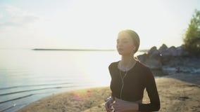 Νέα γυναίκα με smartwatch θαλασσίως Νέο φίλαθλο κορίτσι που χρησιμοποιεί το έξυπνο ρολόι στην παραλία στο ηλιοβασίλεμα Φλόγα φακώ απόθεμα βίντεο
