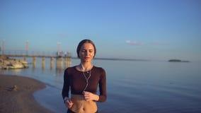 Νέα γυναίκα με smartwatch θαλασσίως Νέο φίλαθλο κορίτσι που χρησιμοποιεί το έξυπνο ρολόι στην παραλία στο ηλιοβασίλεμα Φλόγα φακώ φιλμ μικρού μήκους