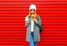 Νέα γυναίκα μόδας αρκετά με το φλυτζάνι καφέ που χρησιμοποιεί το smartphone σε ένα κόκκινο Στοκ φωτογραφία με δικαίωμα ελεύθερης χρήσης