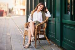 Νέα γυναίκα μόδας στην άσπρη συνεδρίαση πουκάμισων στην ψάθινη καρέκλα Στοκ εικόνα με δικαίωμα ελεύθερης χρήσης