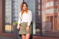 Νέα γυναίκα μόδας στο άσπρο πουκάμισο και την κοντή φούστα στην οδό πόλεων Στοκ Φωτογραφία