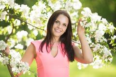 Νέα γυναίκα μόδας άνοιξη Καθιερώνον τη μόδα κορίτσι στα ανθίζοντας δέντρα ι Στοκ Εικόνες
