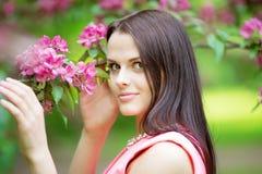 Νέα γυναίκα μόδας άνοιξη Καθιερώνον τη μόδα κορίτσι στα ανθίζοντας δέντρα ι Στοκ Φωτογραφία