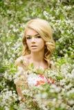 Νέα γυναίκα μόδας άνοιξη Καθιερώνον τη μόδα κορίτσι στα ανθίζοντας δέντρα ι Στοκ Εικόνα