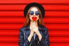 Νέα γυναίκα μόδας αρκετά με την κόκκινη καρδιά lollipop που φορά το σακάκι δέρματος μαύρων καπέλων πέρα από το υπόβαθρο Στοκ Εικόνες