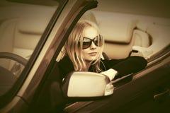 Νέα γυναίκα μόδας στα γυαλιά ηλίου που οδηγούν το μετατρέψιμο αυτοκίνητο Στοκ Εικόνα