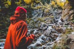 Νέα γυναίκα οδοιπόρων με το φλυτζάνι του τσαγιού κοντά σε έναν ποταμό βουνών Όμορφη φύση στα βουνά στοκ εικόνες