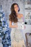 Νέα γυναίκα ομορφιάς με το κιβώτιο δώρων Χριστουγέννων, νέο δέντρο έτους backgr Στοκ Εικόνες