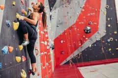 Νέα γυναίκα ορειβατών που αναρριχείται στον πρακτικό βράχο στην αναρρίχηση του κέντρου, Στοκ Φωτογραφία