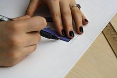 Νέα γυναίκα - ο αρχιτέκτονας σύρει ένα σχέδιο, γραφικό, σχέδιο, γεωμετρικές μορφές από το μολύβι στο μεγάλο φύλλο του εγγράφου στ Στοκ φωτογραφία με δικαίωμα ελεύθερης χρήσης