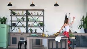 Νέα γυναίκα πιπεροριζών στην πυτζάμα που χορεύει και που πηδά στην κουζίνα, εύθυμος και χαρούμενος, έχοντας τον καλό χρόνο στο σπ απόθεμα βίντεο