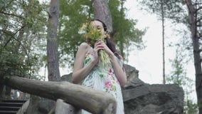 Νέα γυναίκα πορτρέτου αρκετά με τη μακριά μαύρη στάση τρίχας στα ξύλινα σκαλοπάτια και τα άγρια λουλούδια μυρωδιών στο δάσος φιλμ μικρού μήκους