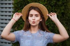 Νέα γυναίκα πορτρέτου αρκετά στο φυσώντας χειλικό φιλί θερινών καπέλων υπαίθριο Στοκ Φωτογραφίες
