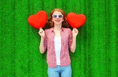 Νέα γυναίκα πορτρέτου με τα κόκκινα μπαλόνια ενός αέρα με μορφή μιας καρδιάς Στοκ φωτογραφία με δικαίωμα ελεύθερης χρήσης