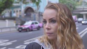 Νέα γυναίκα πορτρέτου με τη σγουρή κόκκινη τρίχα στο υπόβαθρο κυκλοφορίας πόλεων Όμορφη γυναίκα προσώπου που στέκεται στην κίνηση φιλμ μικρού μήκους