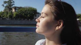 Νέα γυναίκα πορτρέτου που κλείνει τα μάτια της που απολαμβάνουν τις ακτίνες ήλιων που επιπλέουν στον ποταμό φιλμ μικρού μήκους