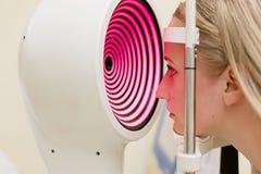 Νέα γυναίκα που έχει τα μάτια της εξετασμένων από ένα μάτι Στοκ φωτογραφία με δικαίωμα ελεύθερης χρήσης