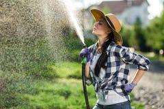 Νέα γυναίκα που έχει τη διασκέδαση ενώ οι εγκαταστάσεις ποτίσματος στον κήπο στρέφονται στοκ φωτογραφία με δικαίωμα ελεύθερης χρήσης