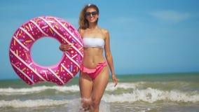 Νέα γυναίκα που έχει τη διασκέδαση με διογκώσιμο doughnut δαχτυλιδιών παιχνιδιών στην παραλία απόθεμα βίντεο