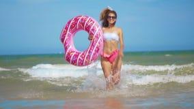 Νέα γυναίκα που έχει τη διασκέδαση με διογκώσιμο doughnut δαχτυλιδιών παιχνιδιών στην παραλία φιλμ μικρού μήκους