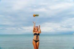 Νέα γυναίκα που έχει τη διασκέδαση με τους ανανάδες στην παραλία Στοκ Εικόνες