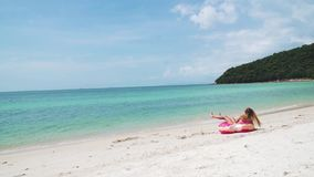 Νέα γυναίκα που έχει τη διασκέδαση με το διογκώσιμο δαχτυλίδι στην παραλία φιλμ μικρού μήκους