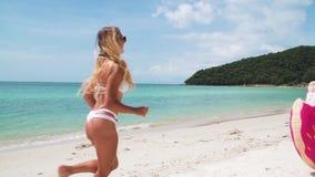 Νέα γυναίκα που έχει τη διασκέδαση με το διογκώσιμο δαχτυλίδι στην παραλία απόθεμα βίντεο