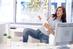 Νέα γυναίκα που έχει τη διασκέδαση στο φωτεινό γραφείο