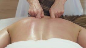 Νέα γυναίκα που έχει το πίσω μασάζ αντι cellulite στο σαλόνι SPA ομορφιάς Η μασέρ κάνει cellulite το μασάζ σε μια νεολαία φιλμ μικρού μήκους