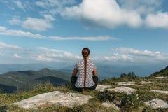 Νέα γυναίκα που ή που κάνει η γιόγκα ενώ κάθεται στην κορυφή βράχου με το μαγικό τοπίο βουνών στοκ φωτογραφίες με δικαίωμα ελεύθερης χρήσης