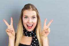 Νέα γυναίκα που δίνει το σημάδι ειρήνης Στοκ Εικόνες