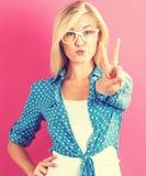 Νέα γυναίκα που δίνει το σημάδι ειρήνης Στοκ Φωτογραφία