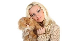 Νέα γυναίκα που αγκαλιάζει μια μεγάλη μαλακή κόκκινη γάτα Στοκ Εικόνες