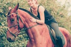 Νέα γυναίκα που αγκαλιάζει και που κάθεται στο άλογο Στοκ φωτογραφίες με δικαίωμα ελεύθερης χρήσης