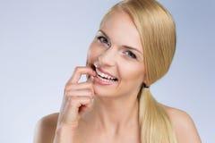 Νέα γυναίκα που δαγκώνει το χαμόγελο δάχτυλών της στοκ φωτογραφία με δικαίωμα ελεύθερης χρήσης