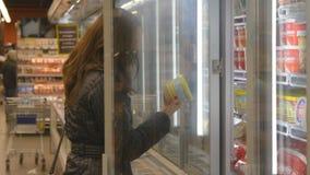 Νέα γυναίκα που αγοράζει τα γαλακτοκομικά ή κατεψυγμένα παντοπωλεία στην υπεραγορά στην κατεψυγμένη πόρτα γυαλιού τμημάτων ανοίγο φιλμ μικρού μήκους