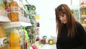 Νέα γυναίκα που αγοράζει το μεταλλικό νερό απόθεμα βίντεο