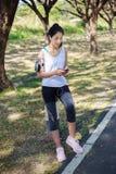 Νέα γυναίκα που ακούει τη μουσική με τα ακουστικά στο έξυπνο τηλέφωνο app Στοκ Φωτογραφίες