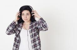 Νέα γυναίκα που ακούει τη μουσική με τα μεγάλα ακουστικά, το κράτημα των χεριών τους και στις δύο πλευρές και το χαμόγελο στοκ φωτογραφία με δικαίωμα ελεύθερης χρήσης