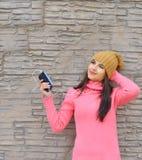 Νέα γυναίκα που ακούει τη μουσική στα ακουστικά στοκ φωτογραφία με δικαίωμα ελεύθερης χρήσης